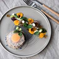 Ravioli z kiszonego ogórka nadziane siekanym ozorkiem cielęcym i żółtkiem sous vide, z sałatką z nasturcji, szczawiu i wędzonego