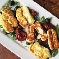 Ser halloumi grillowany podany na rukoli z pomidorami suszonymi i oliwkami