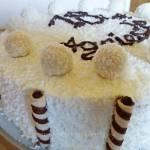Tort urodzinowy z bitą śmietaną, kulkami i wiórkami kokosowymi