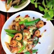 Kremowe risotto z dodatkiem pesto, z karmelizowaną szalotką i groszkiem cukrowym. z krewetkami w sosie pesto i chipsem z szynki