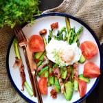 Jak przygotować idealne szparagi? Szparagi zawijane w szynkę parmeńską z jajkiem w koszulce, awokado i pomidorami.