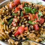 ciepła sałatka makaronowa z pesto paprykowym, orzechami, pomidorami i bazylią