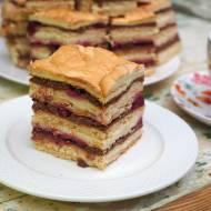 Ciasto przekładane kremem waniliowym i czekoladowym z wiśniami.