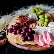 Deska serów i wędlin z krakersami i winogrona