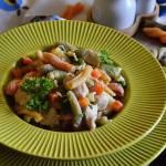 Kolorowy makaron w sosie śmietanowym z kurczakiem, cukinią i groszkiem.